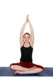 Yoga practicante de la mujer joven en una estera azul Fotografía de archivo