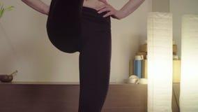 Yoga practicante de la mujer joven equilibrio permanente de la Uno-pierna almacen de video