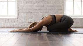 Yoga practicante de la mujer joven, mintiendo en actitud del niño, ejercicio de Balasana imagen de archivo libre de regalías