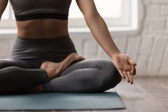 Yoga practicante de la mujer joven, sentándose en la actitud de Padmasana, ejercicio de Lotus fotografía de archivo