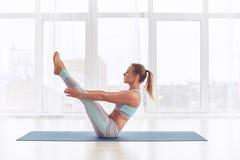 Yoga practicante de la mujer joven, sentándose en el ejercicio de Paripurna Navasana en el estudio de la yoga imagen de archivo