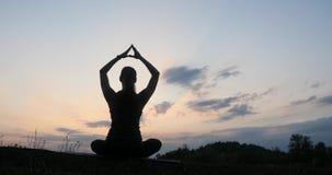 Yoga practicante de la mujer joven de la silueta en la puesta del sol almacen de video