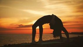 Yoga practicante de la mujer joven de la silueta en la puesta del sol en el mar Momentos felices de la vida - yoga de la silueta  metrajes