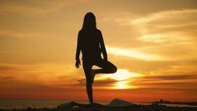Yoga practicante de la mujer joven de la silueta en la puesta del sol en el mar Momentos felices de la vida - yoga de la silueta  almacen de video