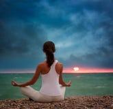 Yoga practicante de la mujer por el mar en la puesta del sol Fotografía de archivo libre de regalías