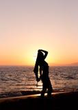 Yoga practicante de la mujer, puesta del sol en la playa Fotografía de archivo