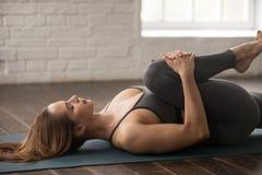Yoga practicante de la mujer, rodillas a la actitud del pecho, Apanasana, cierre para arriba imagen de archivo