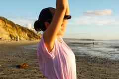 Yoga practicante de la mujer sana joven en la playa en la puesta del sol fotos de archivo libres de regalías