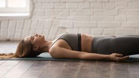 Yoga practicante de la mujer, Savasana, actitud del cadáver, cierre para arriba imagenes de archivo