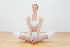 Yoga practicante de la mujer tranquila que se sienta en la posición de loto respecto a piso Fotos de archivo