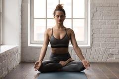 Yoga practicante de la mujer tranquila, sentándose en la actitud de Padmasana, ejercicio de Lotus foto de archivo
