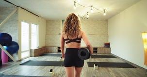 Yoga practicante de la señora joven ella que viene en un estudio de la yoga con su propia estera del deporte tener un rato de la  almacen de video