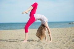 Yoga practicante de la señora joven Entrenamiento cerca del mar del océano Imágenes de archivo libres de regalías