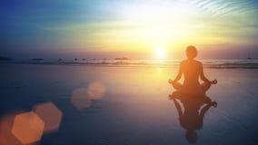 Yoga practicante de la silueta de la mujer en la playa en la puesta del sol asombrosa Imágenes de archivo libres de regalías