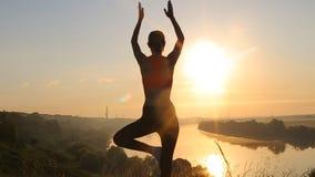 Yoga practicante de la silueta de la mujer joven en la puesta del sol almacen de video
