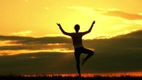 Yoga practicante de la silueta de la mujer joven en el prado en la puesta del sol La muchacha con una figura delgada practica yog almacen de video