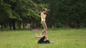 Yoga practicante del acro de los pares hermosos Los instructores jovenes de la yoga practican en un parque de la ciudad en hierba almacen de metraje de vídeo
