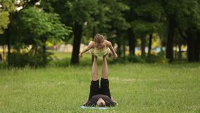 Yoga practicante del acro de los pares hermosos Los instructores jovenes de la yoga practican en un parque de la ciudad en hierba almacen de video