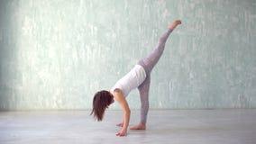 Yoga practicante del adolescente en casa, mujer apta de los jóvenes que hace yoga y que estira ejercicios para entonar para arrib almacen de metraje de vídeo