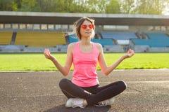 Yoga practicante del adolescente hermoso joven en el estadio Fotos de archivo