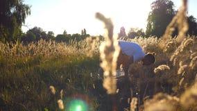 Yoga practicante del hombre joven en la estera Visión a través del campo de hierba el día soleado Individuo deportivo que hace ej almacen de metraje de vídeo