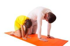 Yoga practicante del papá con la hija aislada Imagen de archivo