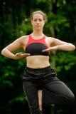 Yoga practicante en un campo verde con los árboles Imagen de archivo libre de regalías