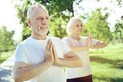 Yoga practicante envejecida sana de la gente junto Imagen de archivo libre de regalías