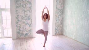 Yoga practicante feliz de la mujer joven Concepto activo sano de la forma de vida Yoga que hace femenina en un estudio con la luz almacen de video