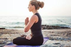 Yoga practicante femenina caucásica joven en la playa fotos de archivo libres de regalías
