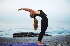 Yoga practicante femenina caucásica joven en la playa imagen de archivo libre de regalías