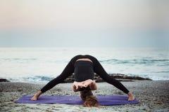 Yoga practicante femenina caucásica joven en la playa fotografía de archivo
