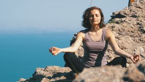 Yoga practicante hermosa y posiciones de la mujer joven al aire libre respecto a un ajuste increíble del top del acantilado almacen de video