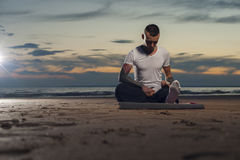 Yoga practicante serena del hombre joven en la playa Foto de archivo libre de regalías