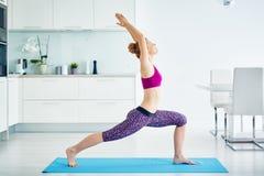 Yoga practicante sonriente de la mujer joven en casa imagenes de archivo