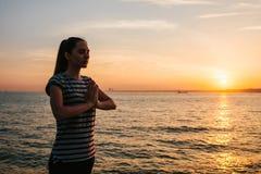 Yoga practicante y meditación de la muchacha hermosa joven al lado del mar en la puesta del sol Deporte Yoga meditación reconstru Imagenes de archivo