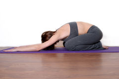 Yoga Practice. A young woman stretches herself out on a yoga mat in a yoga pose Stock Photography