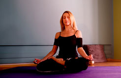 Yoga practice. Blonde woman practicing yoga in a studio Stock Image