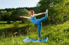 Yoga practice. Red woman practicing fitness yoga Stock Photography