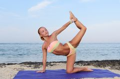 Yoga practice. Slim woman practicing by the sea Stock Photography