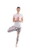 Yoga practice. Smiling yoga girl on white background in vrikshasana (Vriksasana or Tree Pose) using namaste Stock Photos