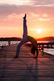 Yoga practice during sunset. On pier Royalty Free Stock Photography