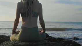 Yoga practice at sunset. Yong woman meditate in lotus pose on the beach. Yoga practice at sunset. Yong woman meditate in lotus pose on the beautiful beach, rear Stock Image