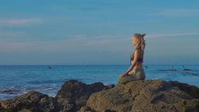 Yoga practice at sunset. Yong woman meditate in lotus pose on the beach. Yoga practice at sunset. Yong woman meditate in lotus pose on the beautiful beach Royalty Free Stock Photography