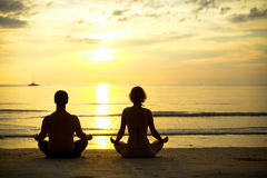 Yoga practice, a young couple sitting on the beach Stock Photos