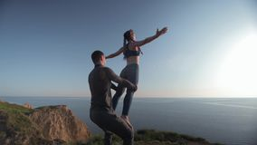 Yoga practices, sports girl with arms raised is balancing on legs of her male partner on background of sea and sky. Yoga practices, sports girl with arms raised stock video