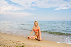 Yoga practicing at the beach. Young woman practicing yoga at the beach Stock Photos