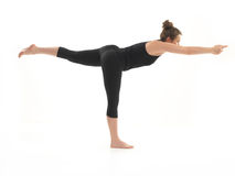 Yoga practitioner. Young, beautiful girl demonstrating difficult yoga posture, dressed in black, on white background Royalty Free Stock Photo