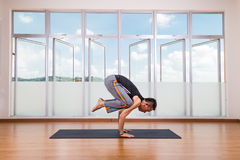 Yoga practitioner performing Crane or Crow pose or Bakasana pose Stock Photography