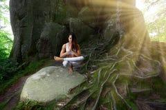 Yoga practiving della giovane donna all'aperto Fotografia Stock